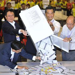 Hong Kong Chief Executive Leung Chun-ying, second right, accompanies with electoral officials, empties a ballot box at the central ballot counting station after Legislative Council elections in Hong Kong, Monday, Sept. 10, 2012. Hong Kong voters cast ballots in legislative elections Sunday that will help determine the eventual shape of full democracy that Beijing has promised the former British colony.