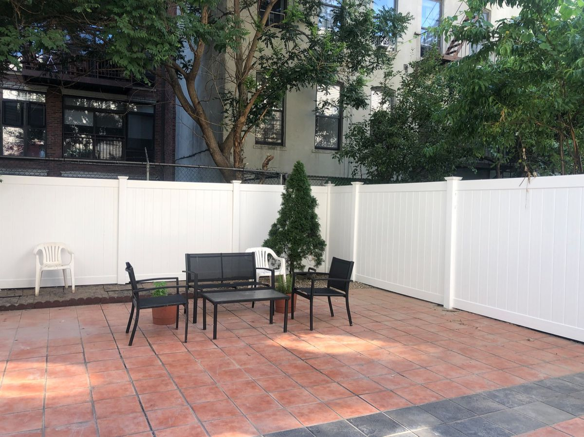 A backyard with pink tiles, a tree, a seating area, and a white fence.