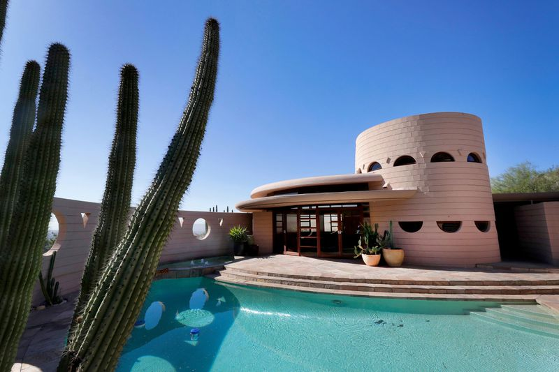 A pool and patio sits adjacent to a stone colored pink house with a cactus in the foreground.