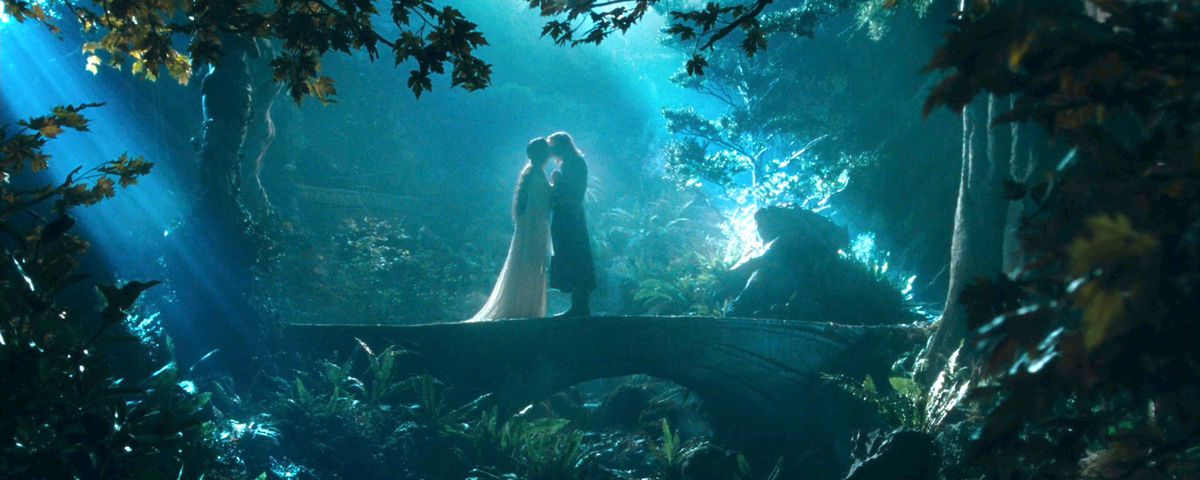 Arwen and Aragorn kiss on a bridge in Rivendell in The Fellowship of the Ring. She is wearing a white dress with a flowing train.