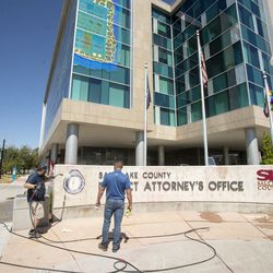 Chad Rasmussen, owner of Royce Industries, and Jason Dixon, sales manager of Royce Industries, clean paint from the sign in front of the Salt Lake County District Attorney's Office building in Salt Lake City on Friday, July 10, 2020. The building suffered tens of thousands of dollars in damage when protesters broke out at least three windows and spread red paint over large portions of the building and area in front of the structure on Thursday.