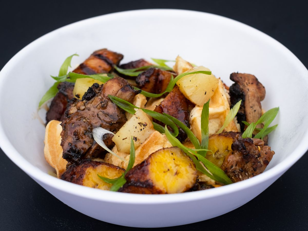 A white bowl filled with charred jerk chicken pieces, slices of golden plantains, and garnished with slices of green onions