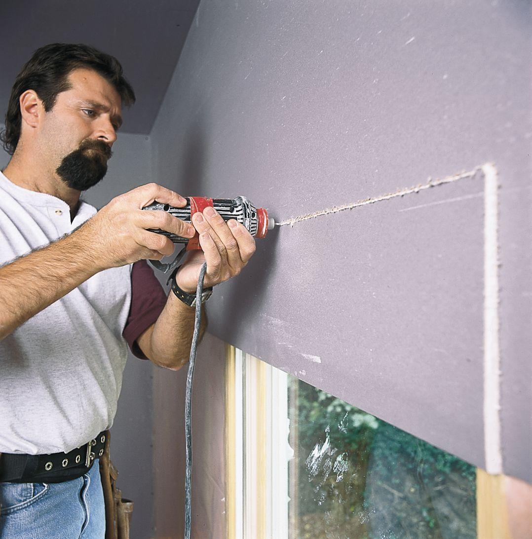 Man Cuts Out Drywall Around Window