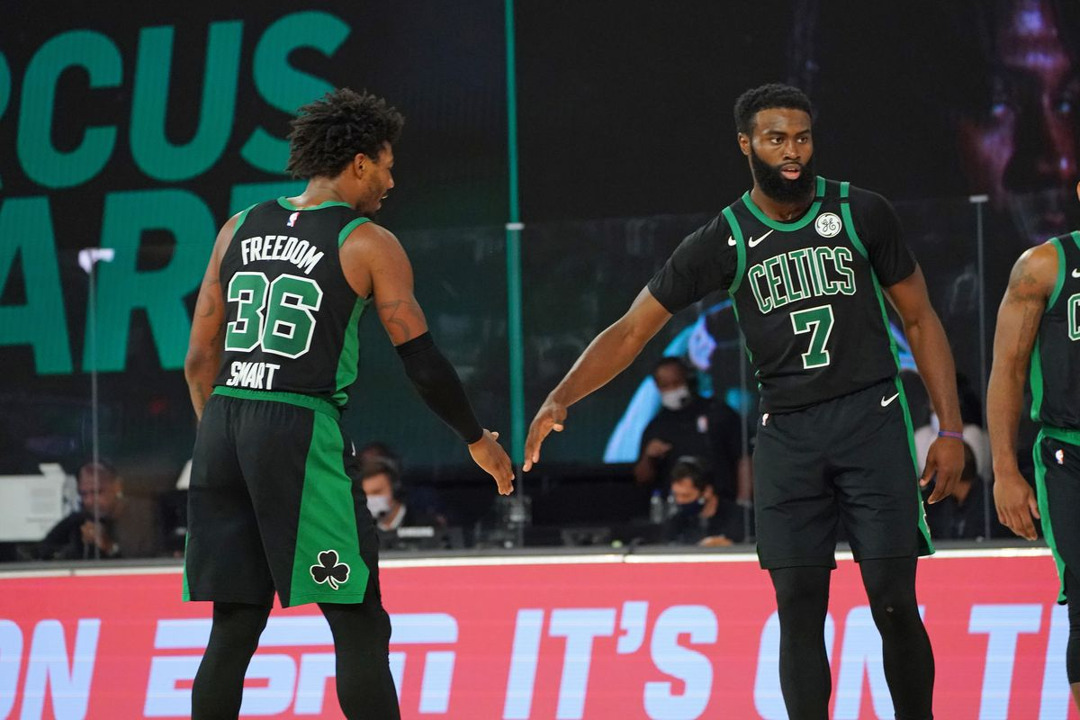 Marcus Smart of the Boston Celtics and Jaylen Brown of the Boston Celtics high-five during a game against the Miami Heat during Game One of the Eastern Conference Finals of the NBA Playoffs on September 15, 2020 at The Field House at ESPN Wide World Of Sports Complex in Orlando, Florida.