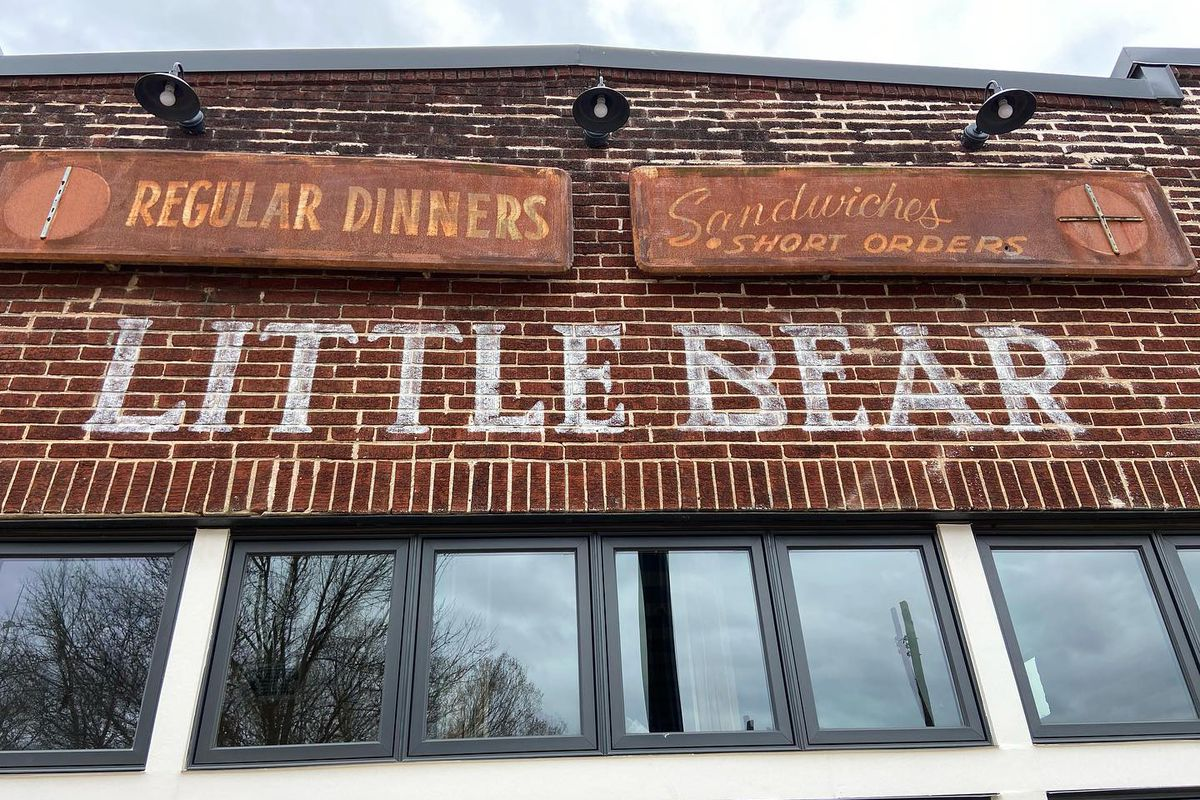 """The handpainted sign for Little Bear with original, rusted signs above reading """"Regular Dinners"""", """"Sandwiches, Short Orders"""""""