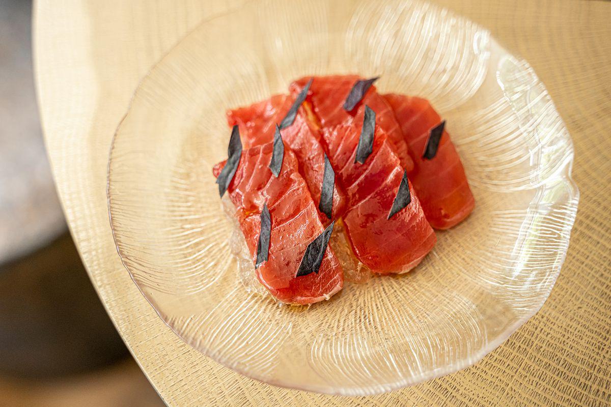Slices of raw big eye tuna with opal basil on a glass plate