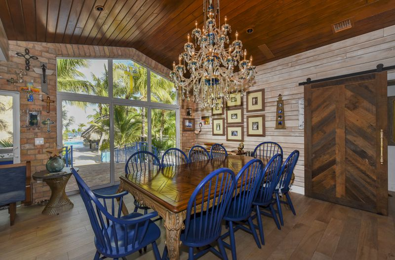 A dining room table with bright blue chairs, a chandelier, and views out to the pool.