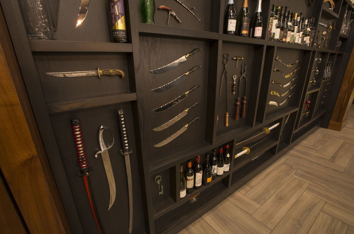Walls decorated with various knives and wine openers