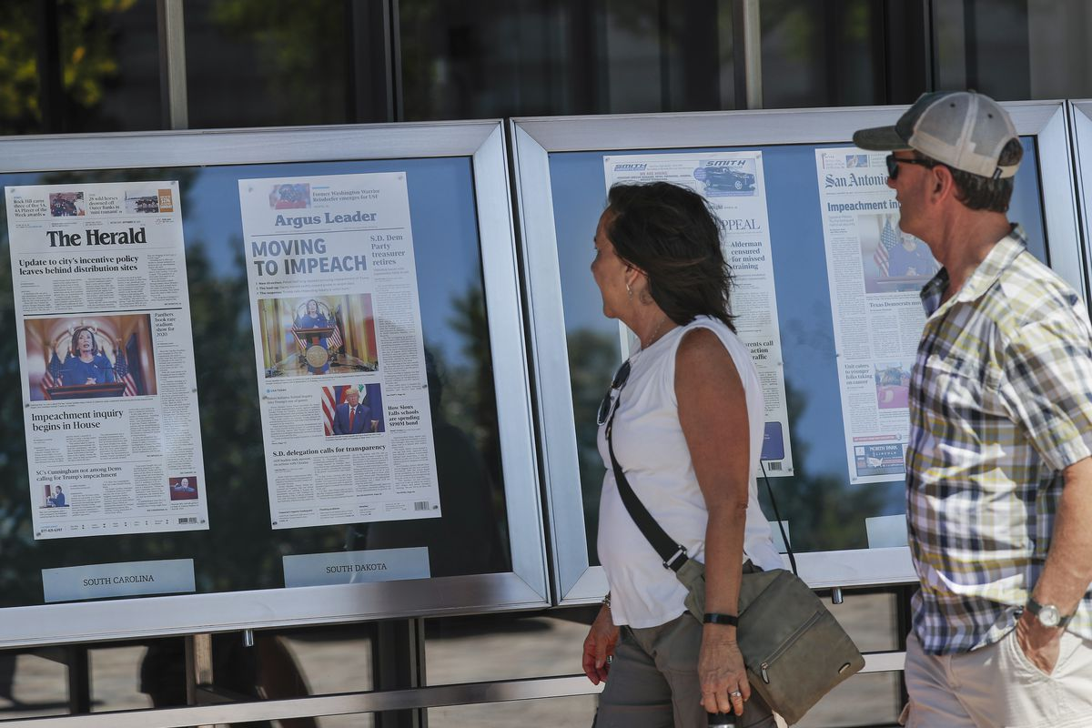 People stop to look at newspaper front pages, from around the United States, on display at the Newseum in Washington, on Sept. 25, 2019.