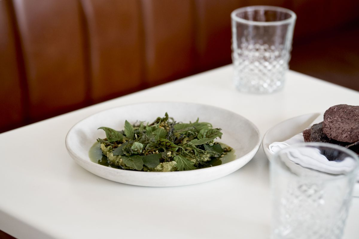 A white plate filled with green guacamole and leafy greens sits on a white table with a dish of purple corn tostadas off to the side