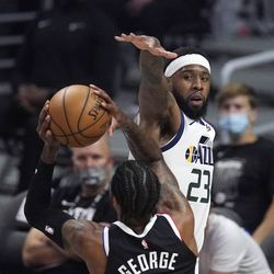 Los Angeles Clippers guard Paul George, left, shoots as Utah Jazz forward Royce O'Neale defends during the first half in Game 6 of a second-round NBA basketball playoff series Friday, June 18, 2021, in Los Angeles.