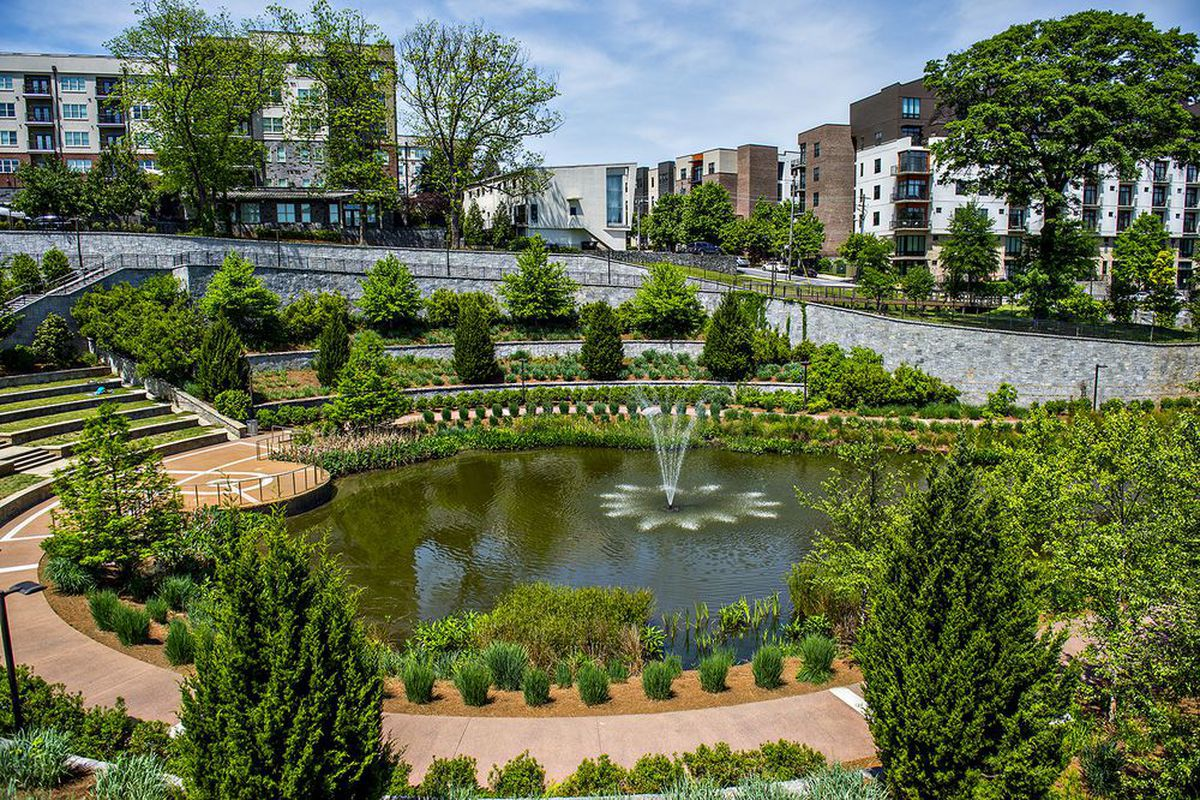 In the foreground is a garden with a pond that has a fountain in the center of it. In the distance are a group of buildings.