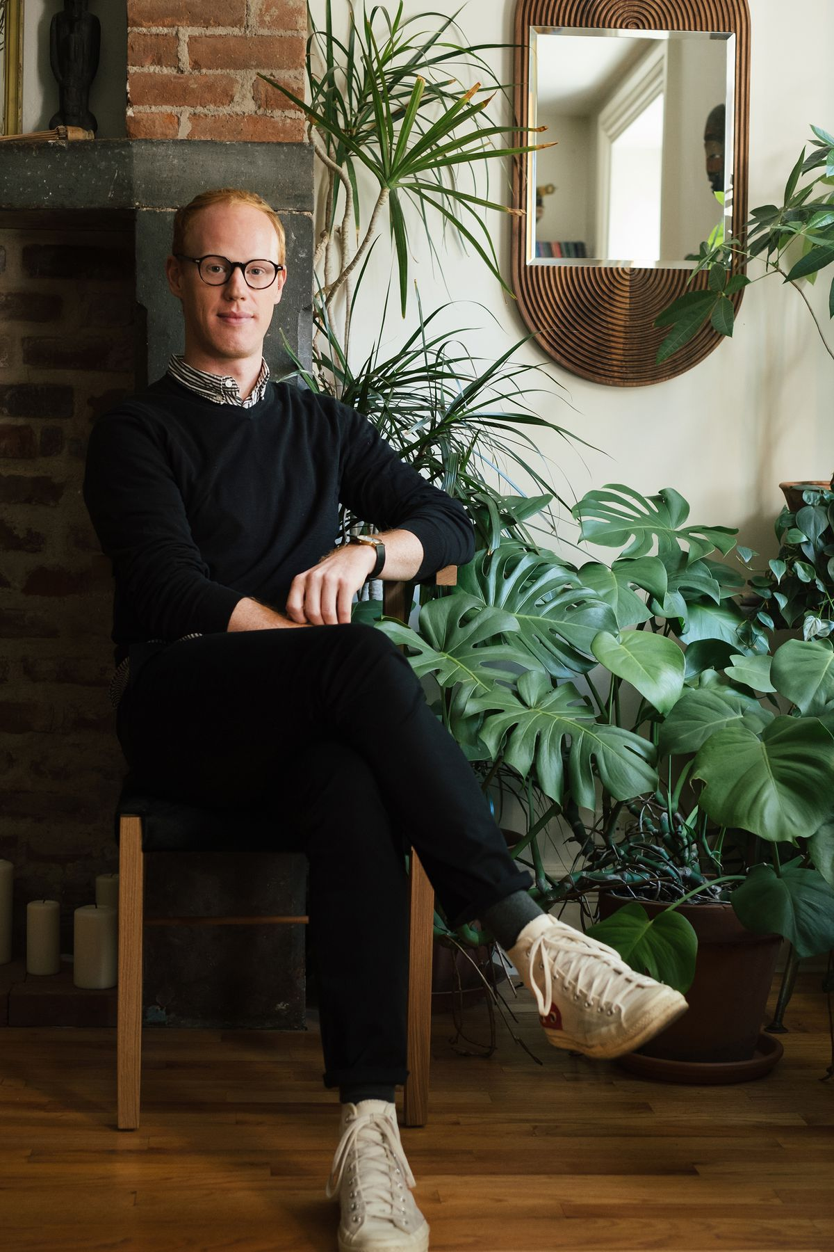 The designer sits beside a number of plant in a chair of his design and beneath a mirror of his design.