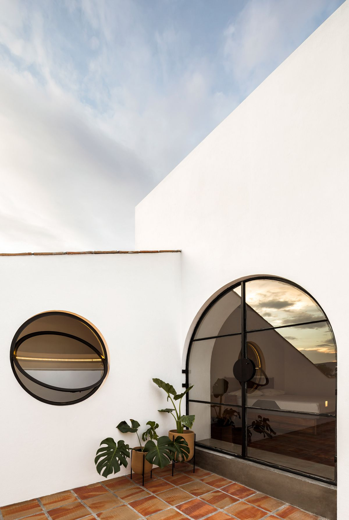 A rooftop terrace with round and arched windows and white walls.