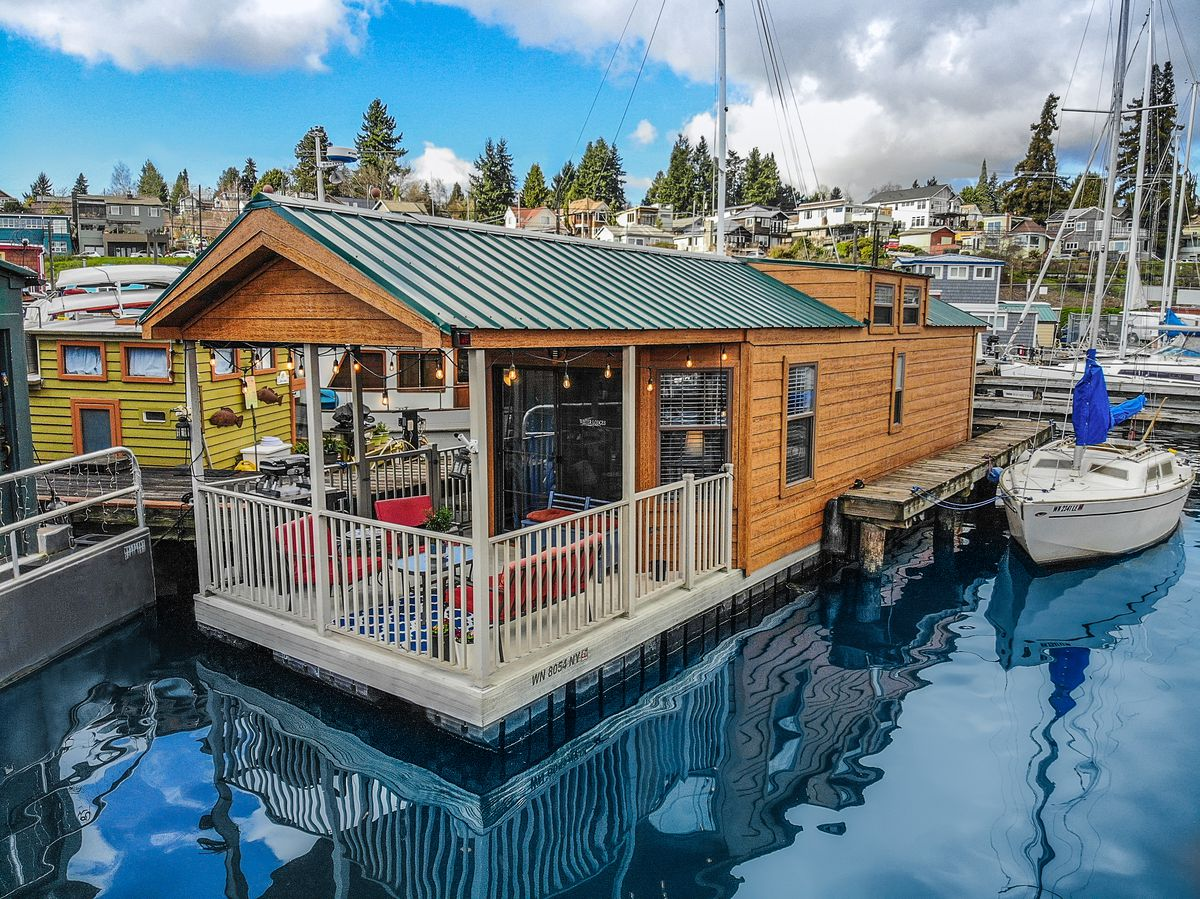 A rear view of a tiny-home like houseboat. There is a covered deck with twinkle lights. A sailboat sits next to the houseboat.
