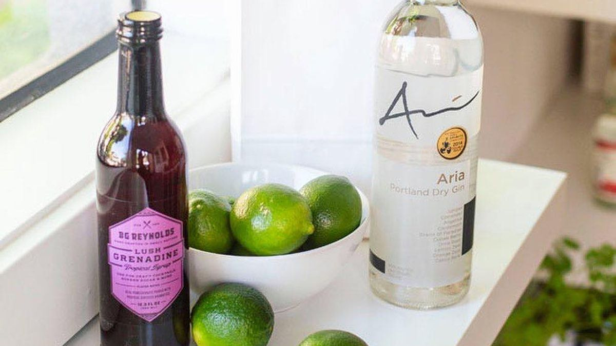 On a white table, a bottle of gin, a BG Reynolds pomegranate syrup bottle, and a bowl of limes sits in front of an Aria-Gin-branded bag.