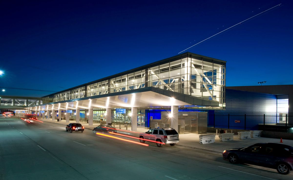 The exterior of the North Terminal at Detroit Metro Airport. The terminal has glass on its upper level. On the lower level are columns and an area for cars to stop and drop off or pick up airport visitors.