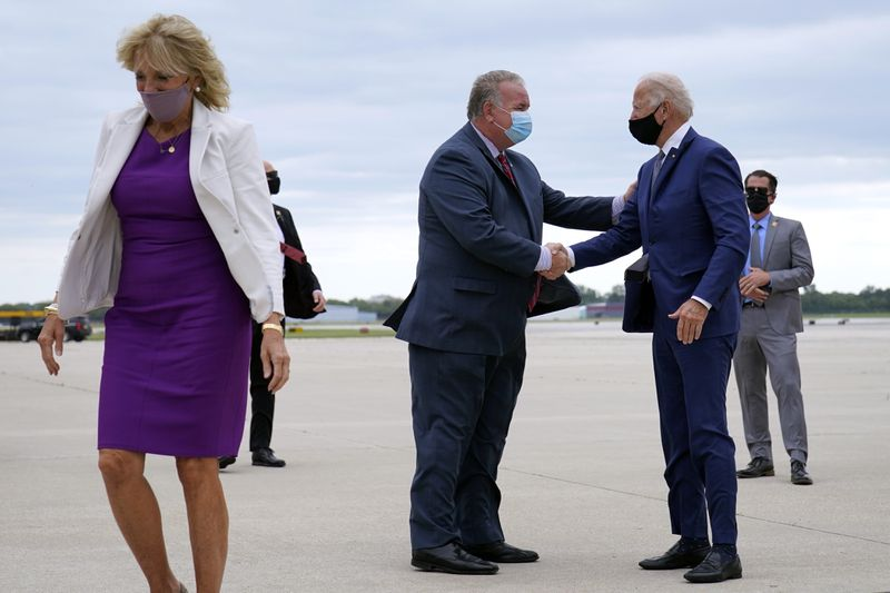 Democratic presidential nominee Joe Biden shakes hands with advance staffer Brian McPartlin as he and his wife Jill Biden, left, arrive at General Mitchell International Airport on Thursday, in Milwaukee.