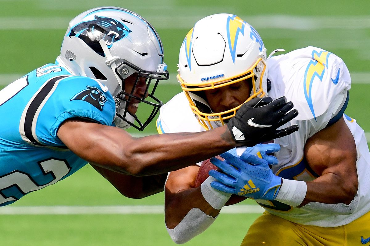 Austin Ekeler #30 of the Los Angeles Chargers takes a hit from Rasul Douglas #24 of the Carolina Panthers during a 21-16 Carolina Panthers win at SoFi Stadium on September 27, 2020 in Inglewood, California.