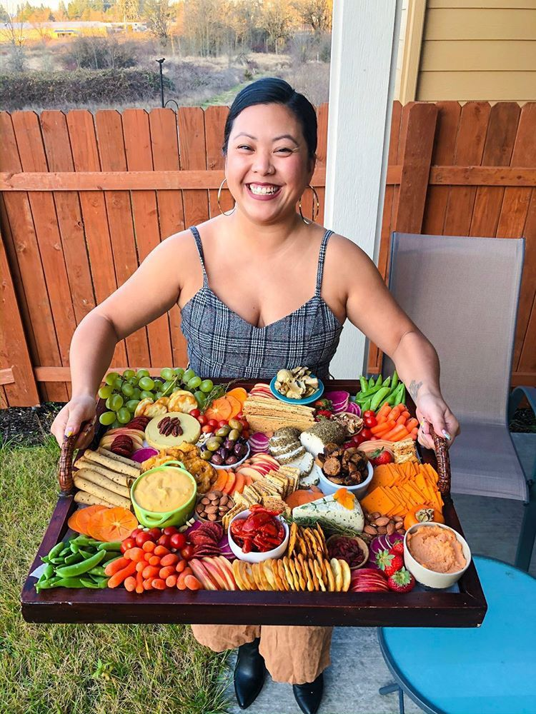 A woman smiles while holding a large plate of vegan charcuterie