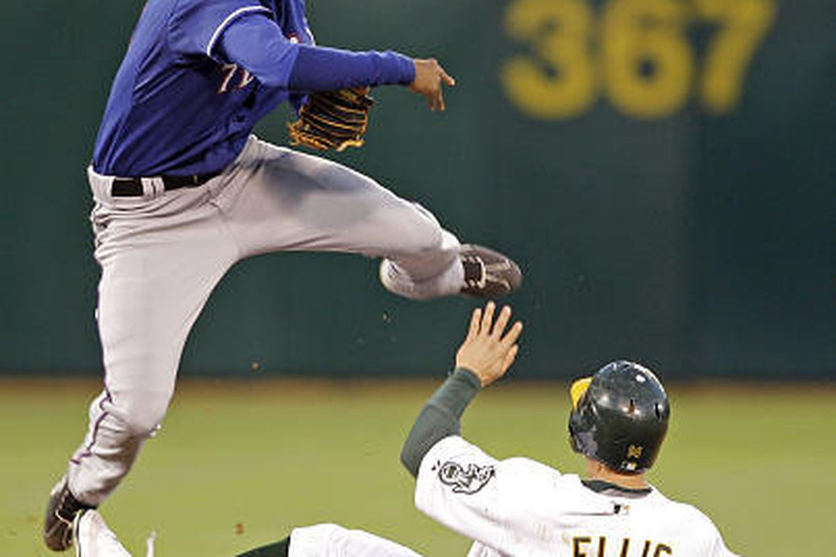 Texas Rangers second baseman Joaquin Arias, left, leaps over Oakland Athletics' Mark Ellis throwing to first to complete a double play in the fourth inning Tuesday.