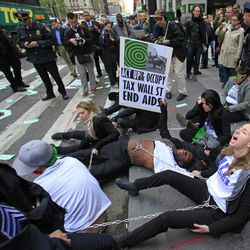 Police prepare to arrest members of a combined group of ACT UP and Occupy Wall Street activists who chained themselves and block traffic at Wall Street and Broadway, near the New York Stock Exchange, on Wednesday, April 25, 2012.  Police used chain cutters and wrestled protesters to the pavement in the middle of Broadway.