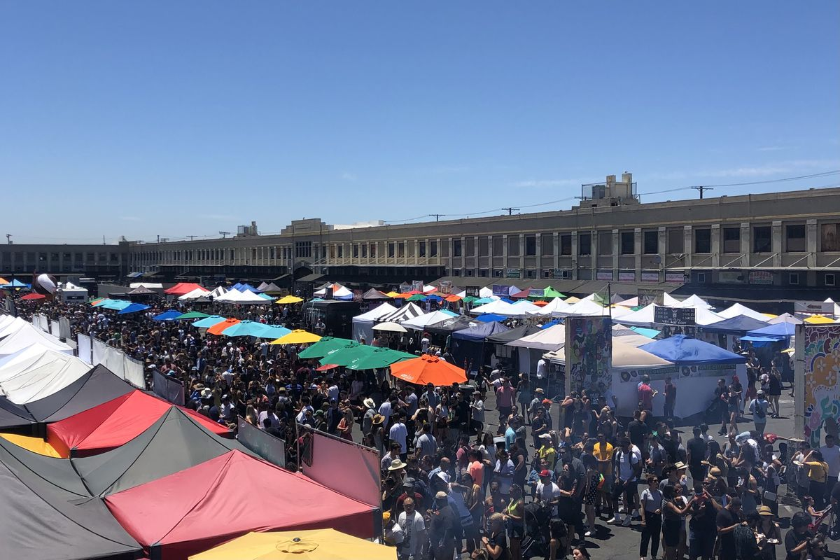 An overhead, angled view of an outdoor food festival, with rows of colorful tents.