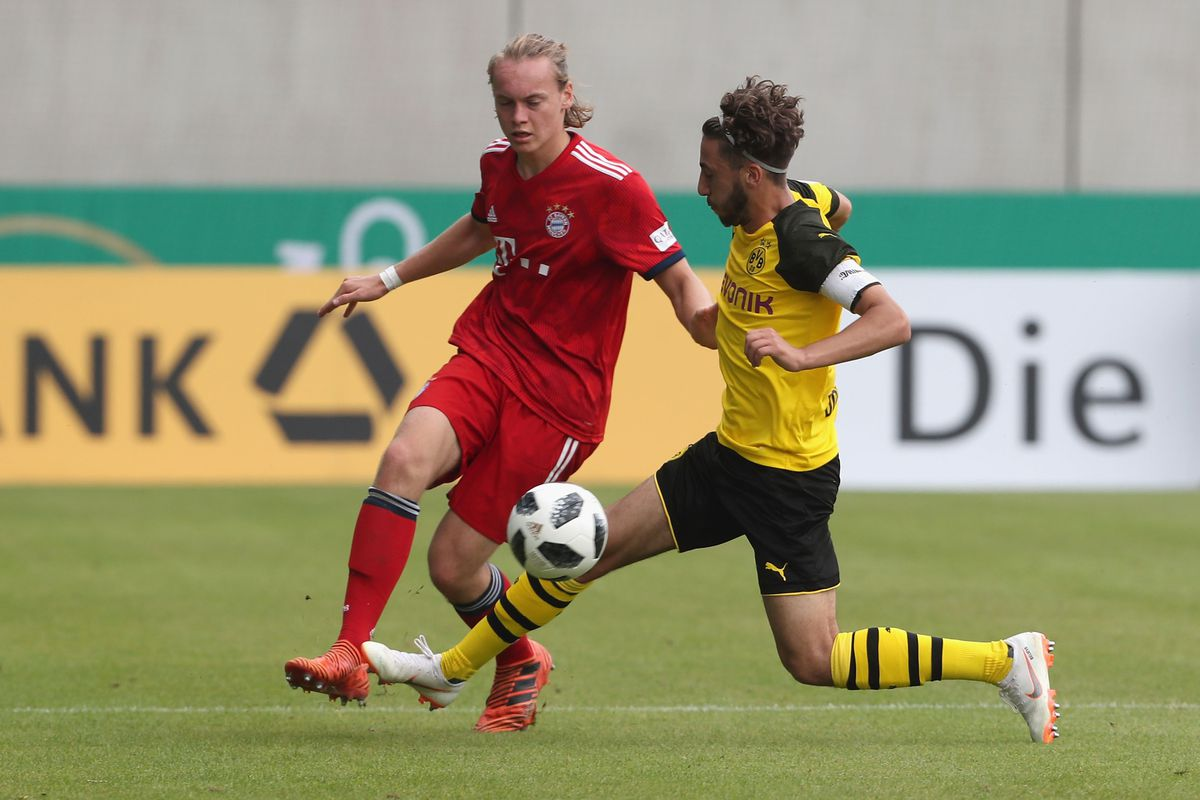 MUNICH, GERMANY - JUNE 17: Ryan Johansson (L) of FC Bayern Muenchen fights for the ball with Alaa Bakir of Borussia Dortmund during the B Juniors German Championship final between FC Bayern Muenchen U17 and Borussia Dortmund U17 on June 17, 2018 in Munich, Germany.