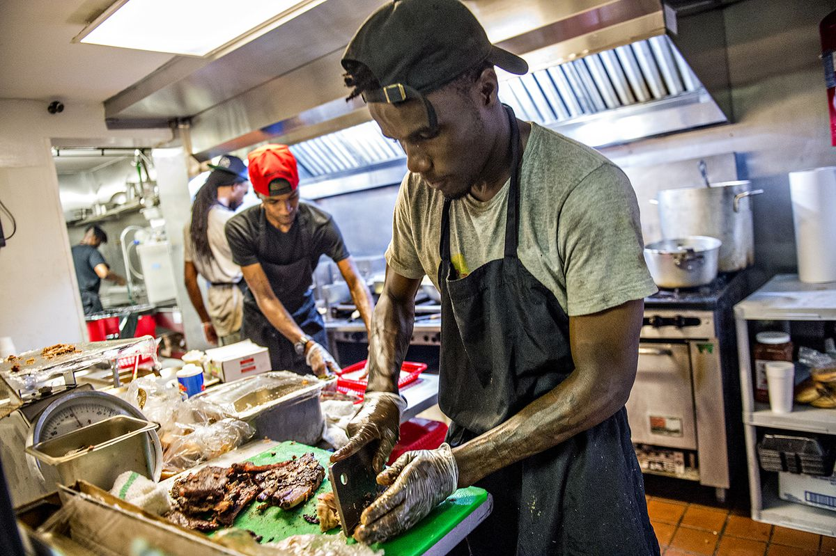 An employee chops smoked ribs and chicken in the kitchen.