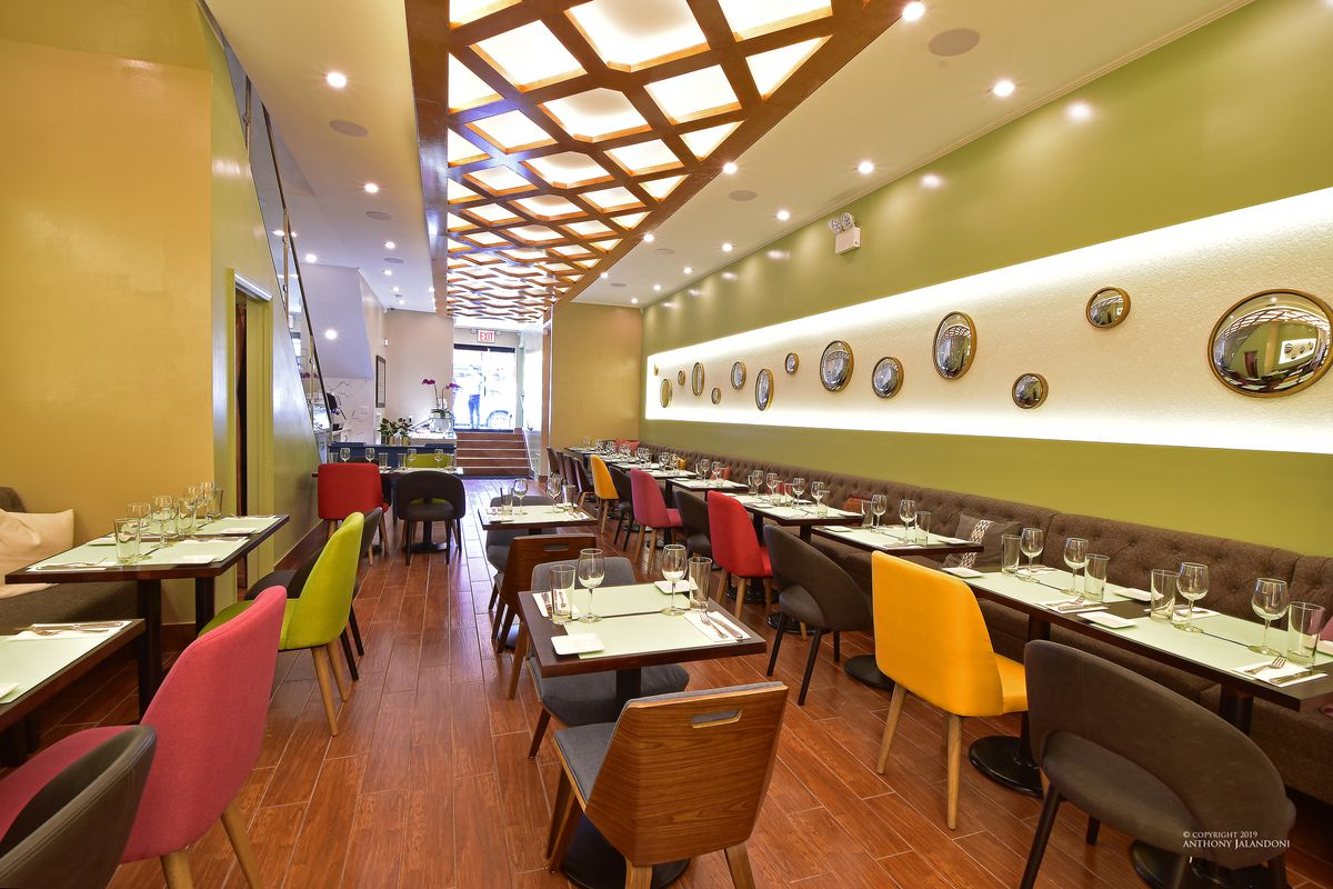 The green interior of a restaurant with colorful chairs and round mirrors on the walls