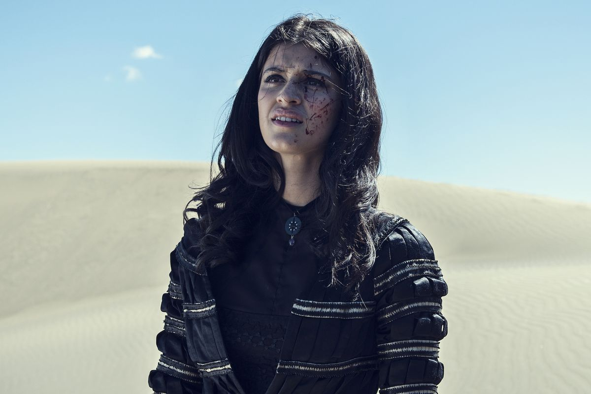 Yennefer stands in a desert, splattered with blood, in The Witcher