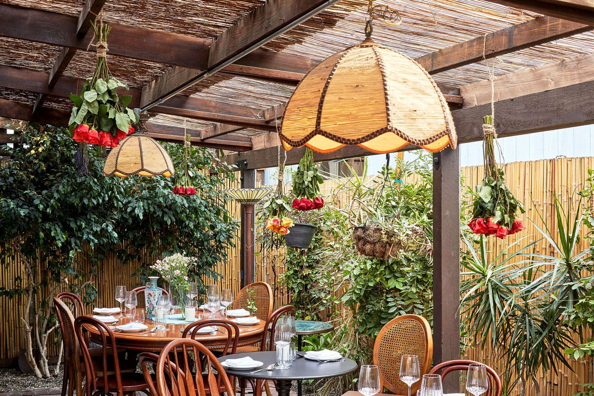 Outdoor patio with pendant lamps, lush greenery to the rear, and backyard style tables.
