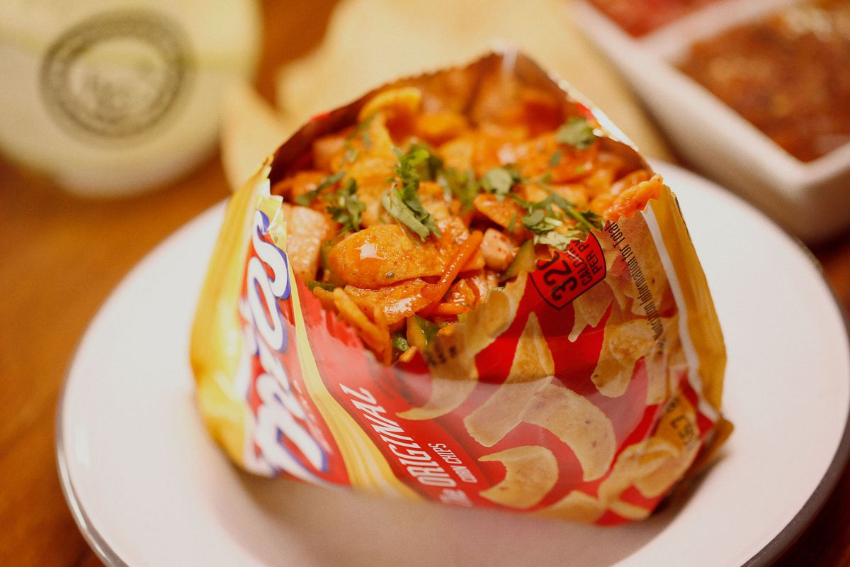 A close-up photo of the Fritos Pie at Cochino Taco consisting of a cut-open bag of Fritos stuffed with Al Pastor, creme, cheddar cheese and black beans