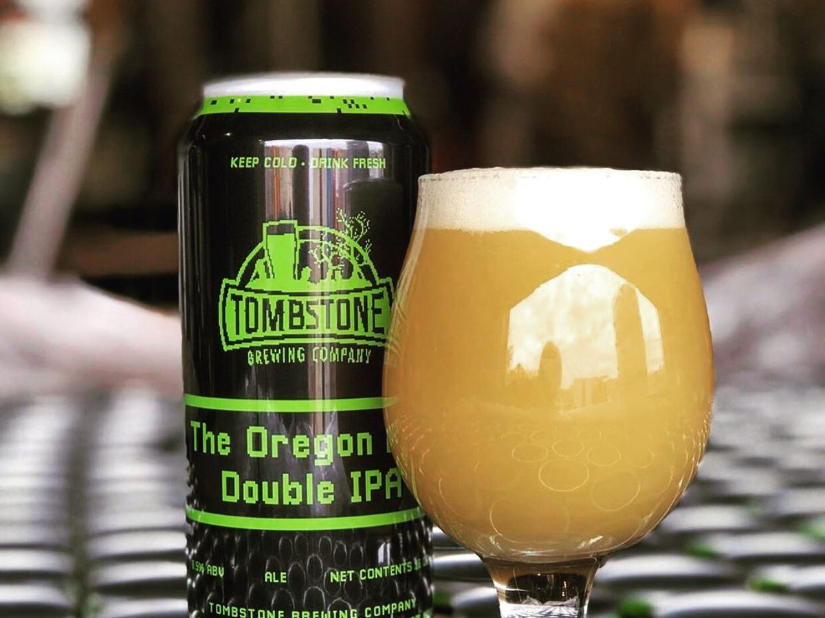 A can of the Oregon Double IPA from Tombstone next to a tulip glass full of the IPA.