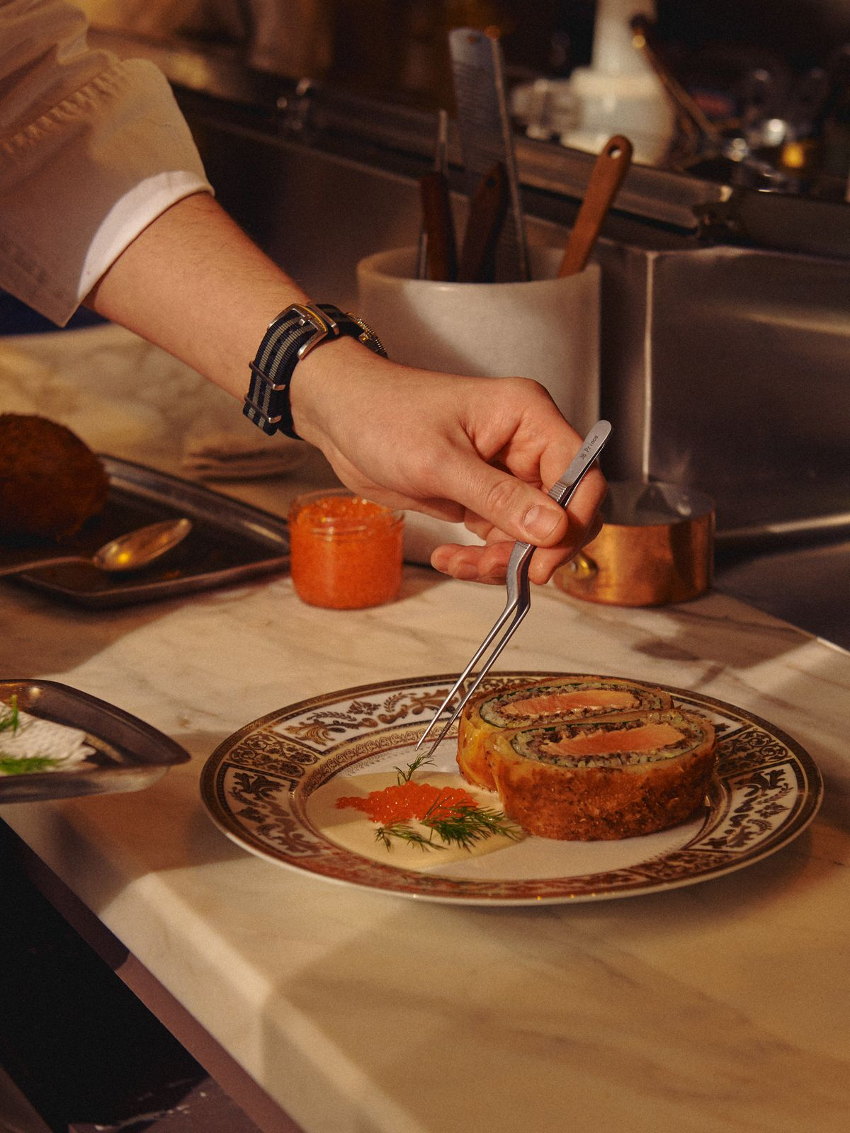 A hand uses tweezers to put dill onto an ornate plate with Russian fish pie.