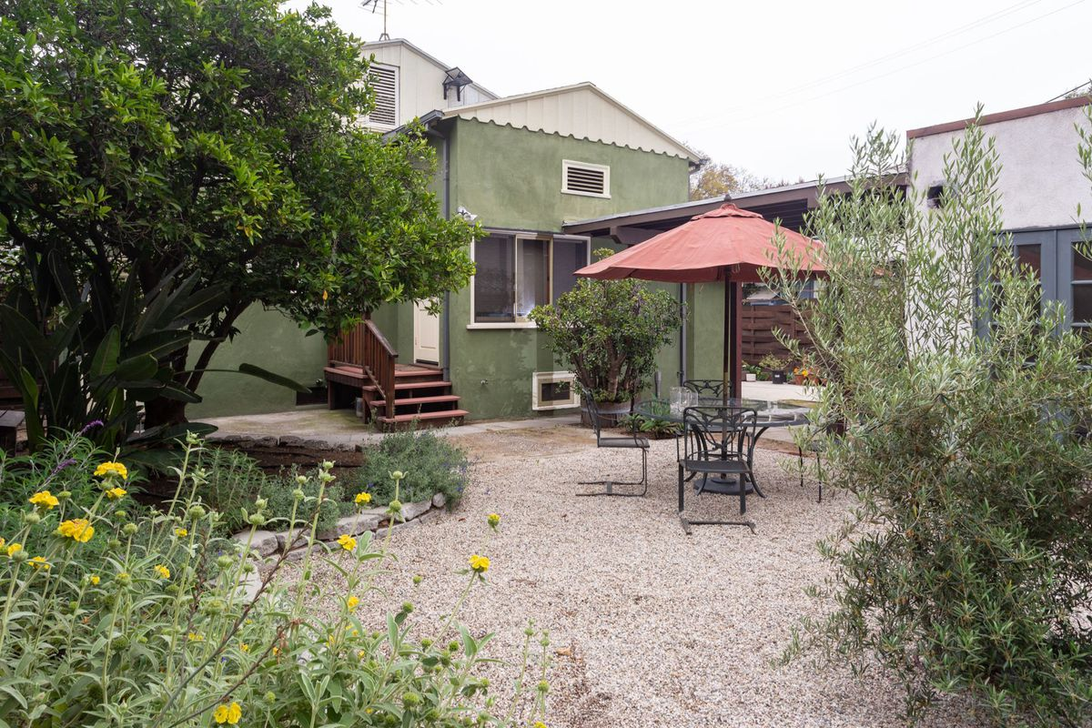 A backyard with gravel, native plants, and a patio.