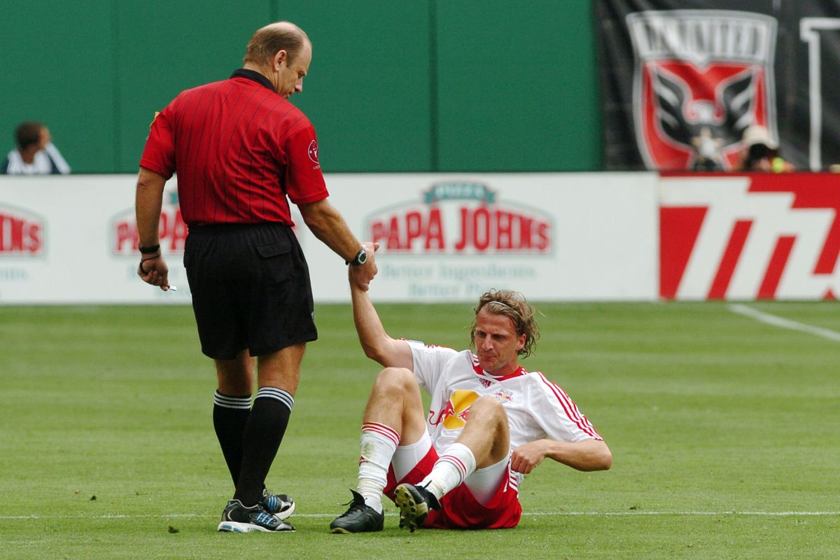 Referee Brian Hall lends a hand to the New York Red Bulls' M