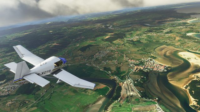 A French-made DR400 over a winding river, its wandering path clearly visible from several thousand feet in the air. The sky is blue with few clouds. From an early pre-alpha of Microsoft Flight Simulator