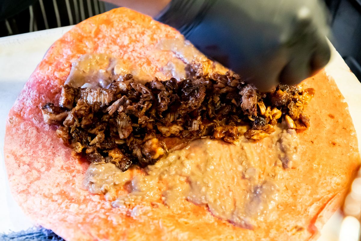Chopped chicken that has been coated in barbecue sauce being arranged on a tortilla by a gloved hand