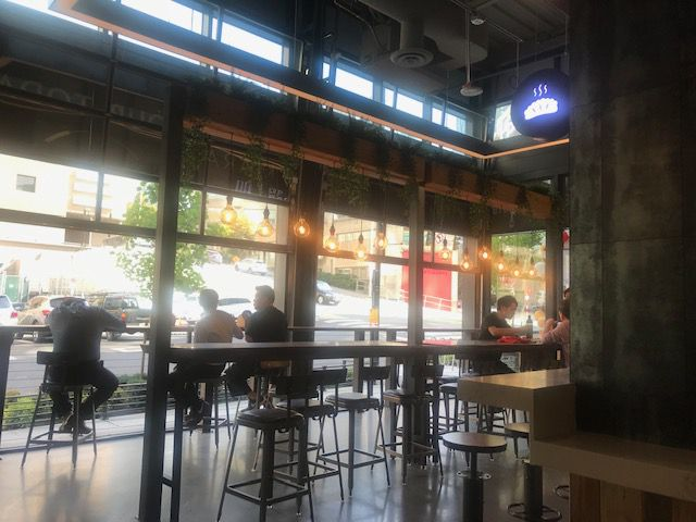 A view of seating by the steam station at H District, with a view looking out onto the street.
