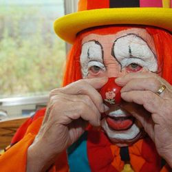 """In this March 29, 2012, photo, Floyd """"Creeky"""" Creekmore puts on his nose while getting dressed before a visit with children at a circus in Billings, Mont. Guinness World Records has anointed the world's oldest performing clown, and it's none other than Creekmore, a former Montana rancher who's been donning the big nose and bright makeup for almost eight decades."""