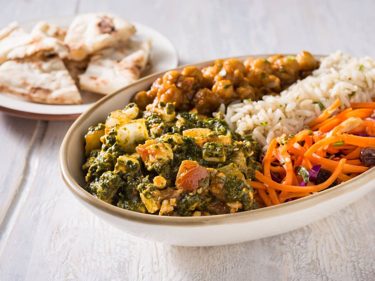 A bowl filled with saag paneer and rice, with naan in the background
