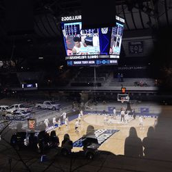 A reflection of BYU and UCLA teams warm up as fans watch in a reflection prior to a first-round game in the NCAA college basketball tournament at Farmers Coliseum in Indianapolis, Saturday, March 20, 2021.
