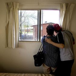 Russ Brown looks out a window of his bedroom in the Clearfield apartment with his mother, Susan Brown, six days after the fire destroyed the home that had belonged to Susan Brown and her parents.