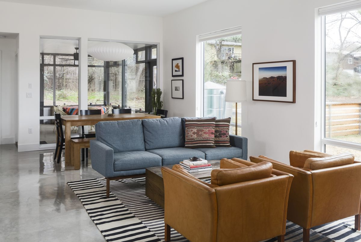 The living room has two leather chairs and a blue sofa.