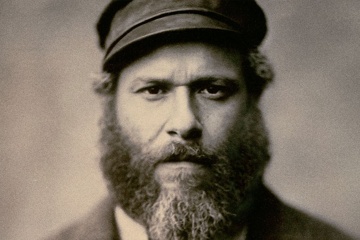 A bearded man wearing a hat in a sepia-toned image.