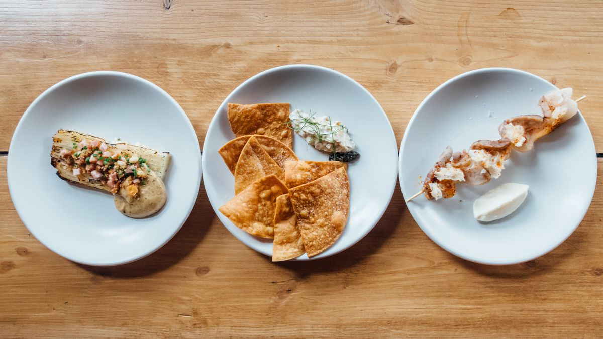 Three plates of food are kept side by side on a wooden table. They're all snack size portions of chips and sandwiches
