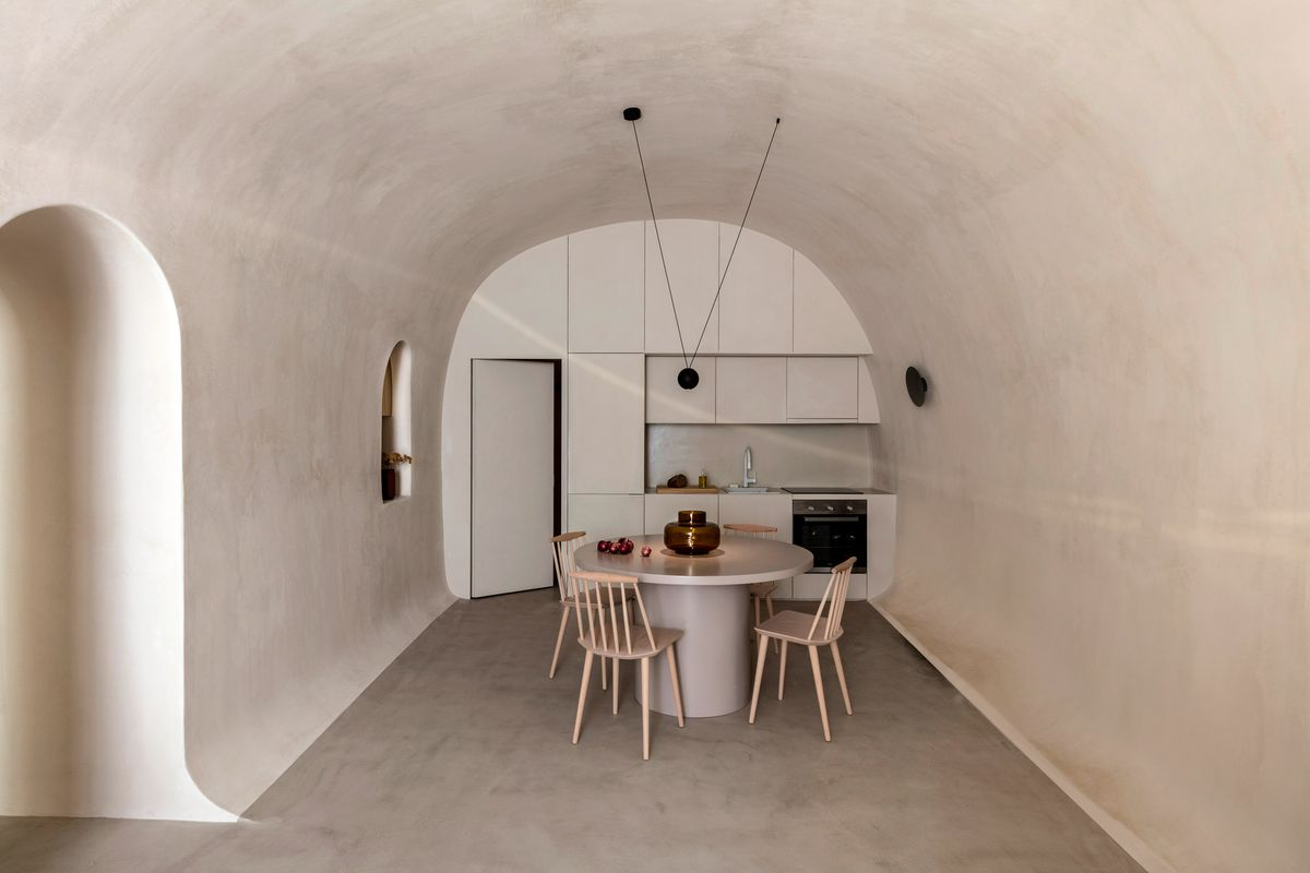 Kitchen with curved ceiling and a small round table.
