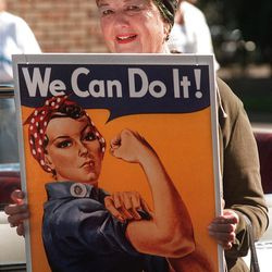 Geraldine Hoff Doyle smiles, posing for a photo with the WWII Rosie the Riveter poster made with her likeness.