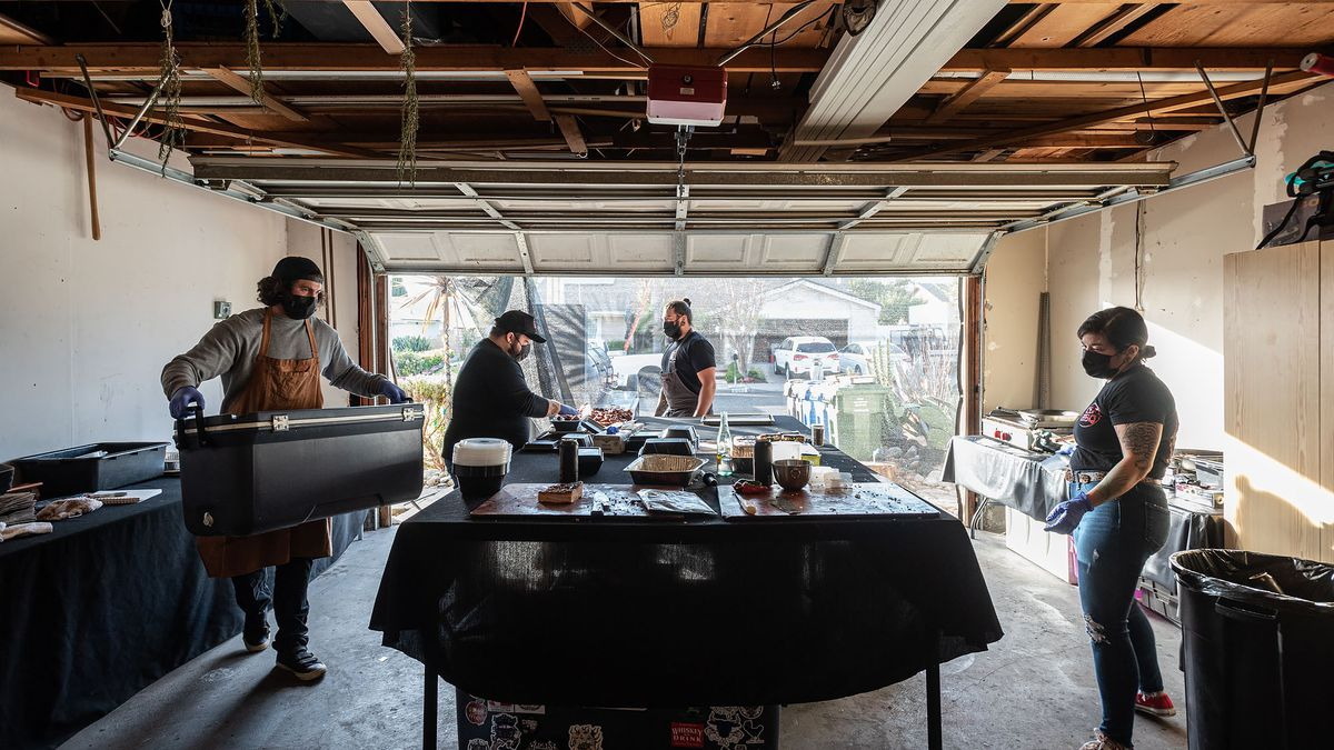 A group works inside of a garage to turn out food.